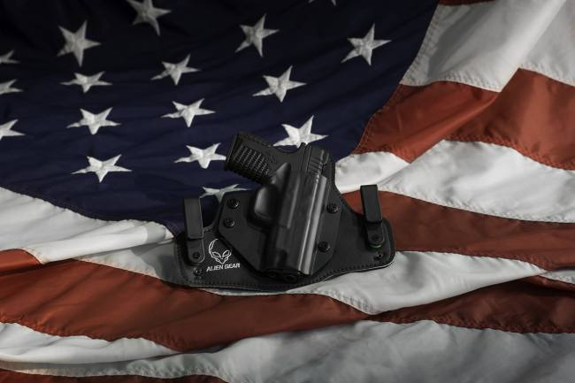 the American flag with gun in holster lying on it