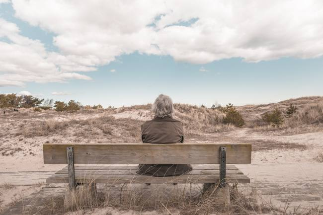 person sitting on a bench in the middle of nowhere