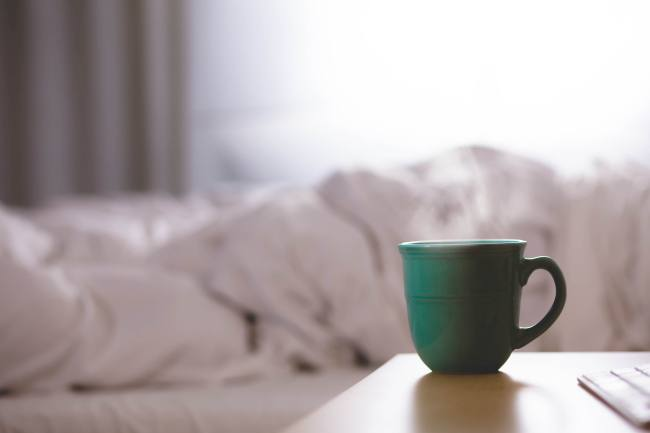 A bed, morning light, and a cup of coffee