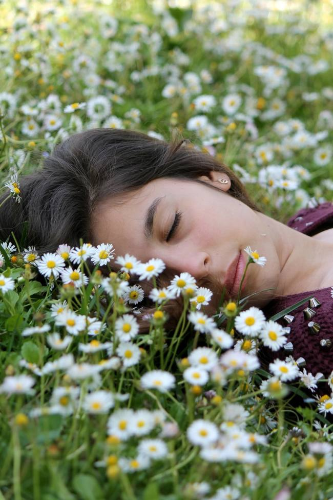 Woman asleep in a field of daises