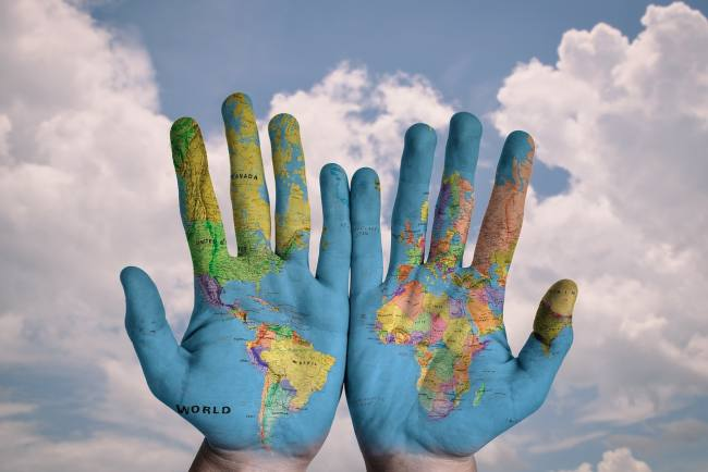 a map of the world imprinted on two hands