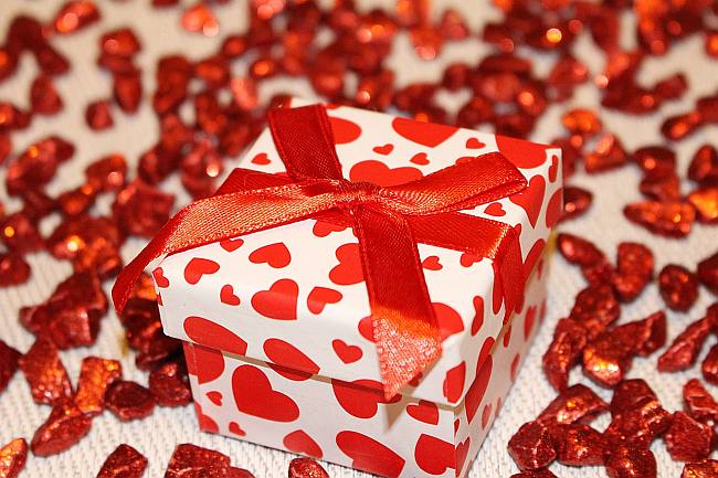 a white gift box with red hearts on it tied up with a red ribbon admist a scattering of sparkly red bark