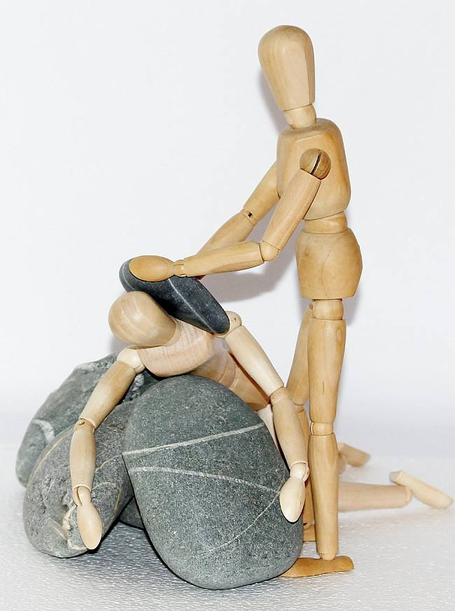image of a wooden person crushing head of another wooden person with a rock