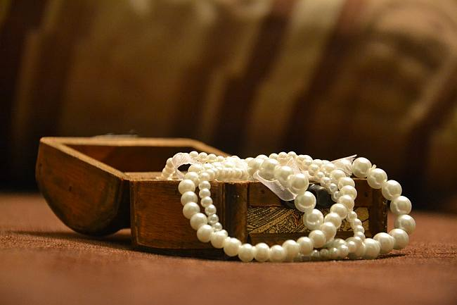 wooden box with strings of pearls spilling out