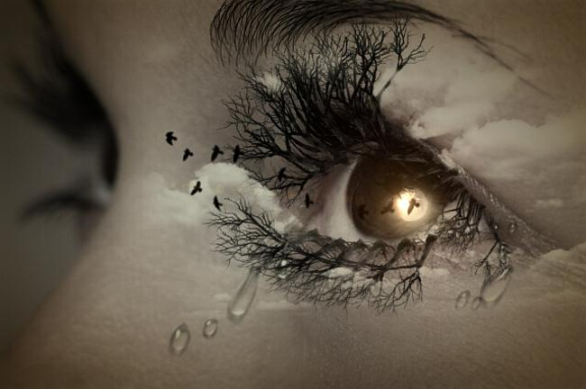 A woman's eye with tears streaming down her face and a flock of black birds flying in/out