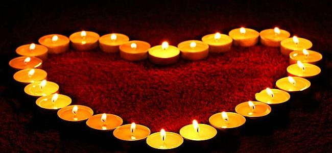 rose petals in the shape of a heart and outlined wiht candles